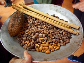 Ingredients being prepped for grinding: cocoa beans, cinnamon, and almonds